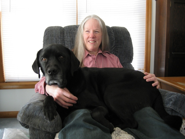Hunter, a Black Lab, Sits in Donna's Lap by Rich Hill