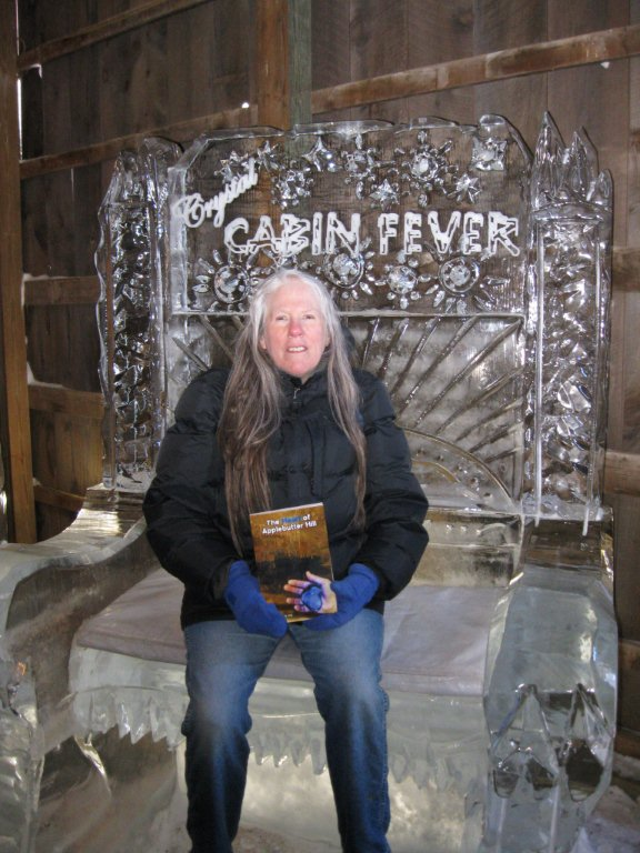 Donna sitting on an ice bench holding a copy of her novel The Heart of Applebutter Hill: photo by Rich Hill