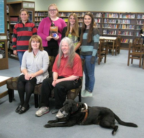 lackawanna trail high library (Factoryville, PA): Donna W. Hill on sofa w librarian kelly hopkins; 4 students (l-r: Taylor Selwood,Jordan Flynn, Ally Decker and Annika Kongvold ) stand behind. Jordan holds Donna's novel The Heart of Applebutter Hill & Donna's black Lab guide dog, Hunter, watches from the floor: photo by rich hill.