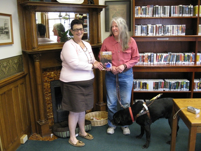 Donna W. Hill donates educator-recommended novel The Heart of Applebutter Hill to Wyalusing Library Dir. Cathy Brady: photo by Rich Hill