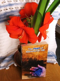 Blooming Amarilis with a print copy of The Heart of Applebutter Hill by Donna W. Hill, a fantasy adventure featuring some awesome flowers: photo by Rich Hill.