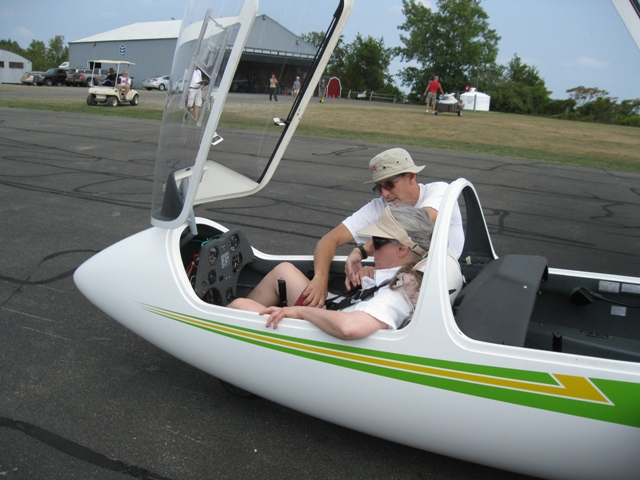 Pre-Flight Instruction at National Soaring Museum in NY: Donna sits in front seat of High-Performance Glider; pilot standing by plane on runway - photo by Rich Hill.