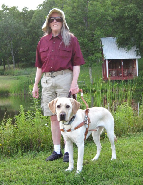 Donna & her new yellow Lab guide dog Mo standing by Hill's pond: photo by Rich Hill