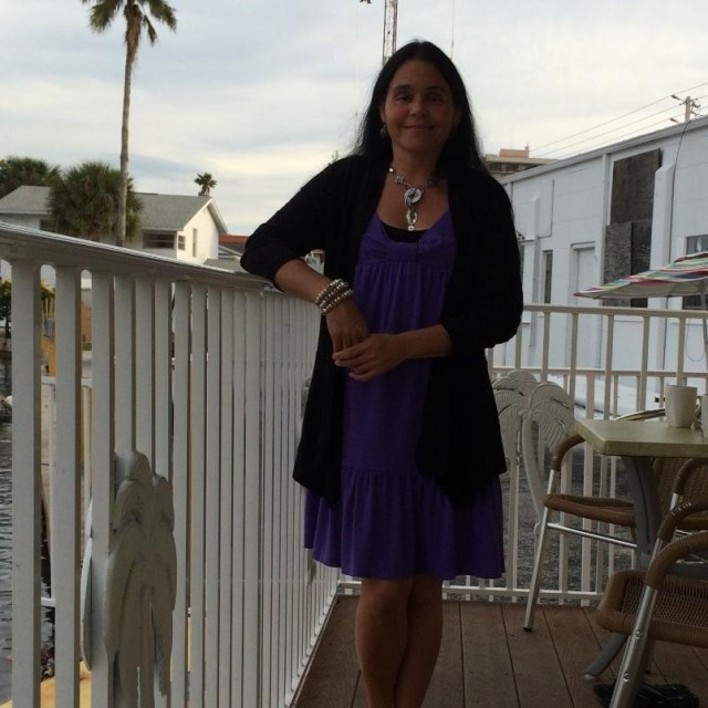 Amy Krout-Horn, author of My Father's Blood, standing beside a patio railing at Boca Ciega Bay, Florida. Amy is wearing a purple, (her favorite color) to-the-knee sundress &silver necklace & earrings. Water & palm trees are visible in distance: photo by Gabriel Horn.